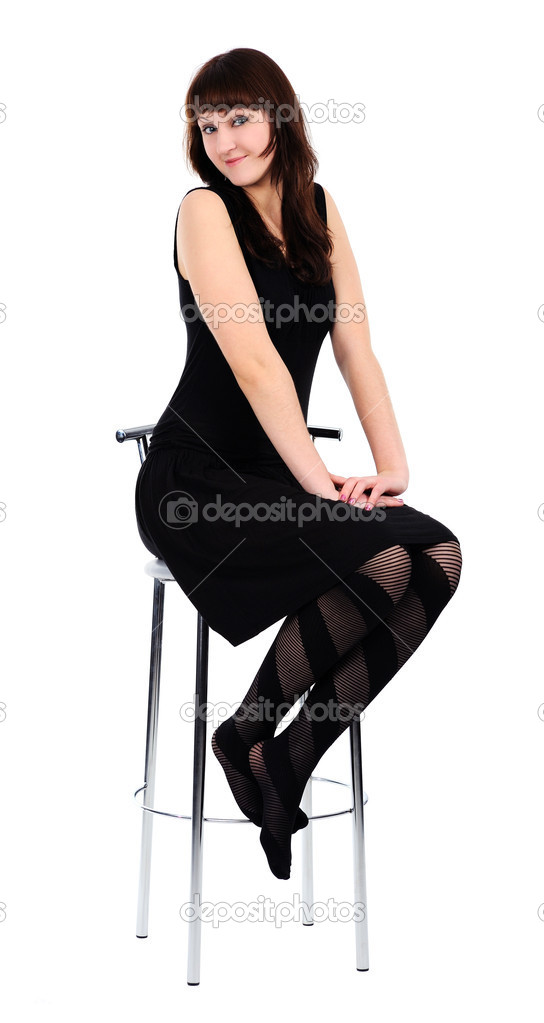 Girl in black dress sitting barefoot on a high chair, isolated on a white background. — Stock Photo #4821628