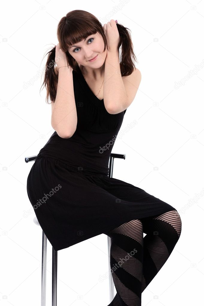 Girl in black dress sitting barefoot on a high chair, isolated on a white background.  Stock Photo #4821634