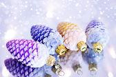 Four decorative pine cones and snowflakes — Stock Photo