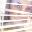 Attractive girl looks out blinds — Stock Photo