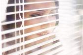 Aantrekkelijk meisje kijkt uit blinds — Stockfoto