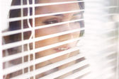 Attractive girl looks out blinds — Stockfoto