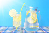 Glass of water with lemon on a blue background — Stock Photo