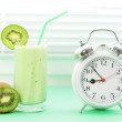 Kiwi juice in a glass and alarm clock on a light background — Stock Photo