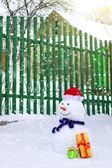 Snowman near house — Stock Photo