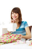 Woman using sewing machine to sew clothing — Stock Photo