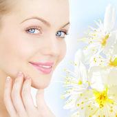 Pielęgnacja skóry. portret młodej kobiety i śliwa kwiaty — Zdjęcie stockowe
