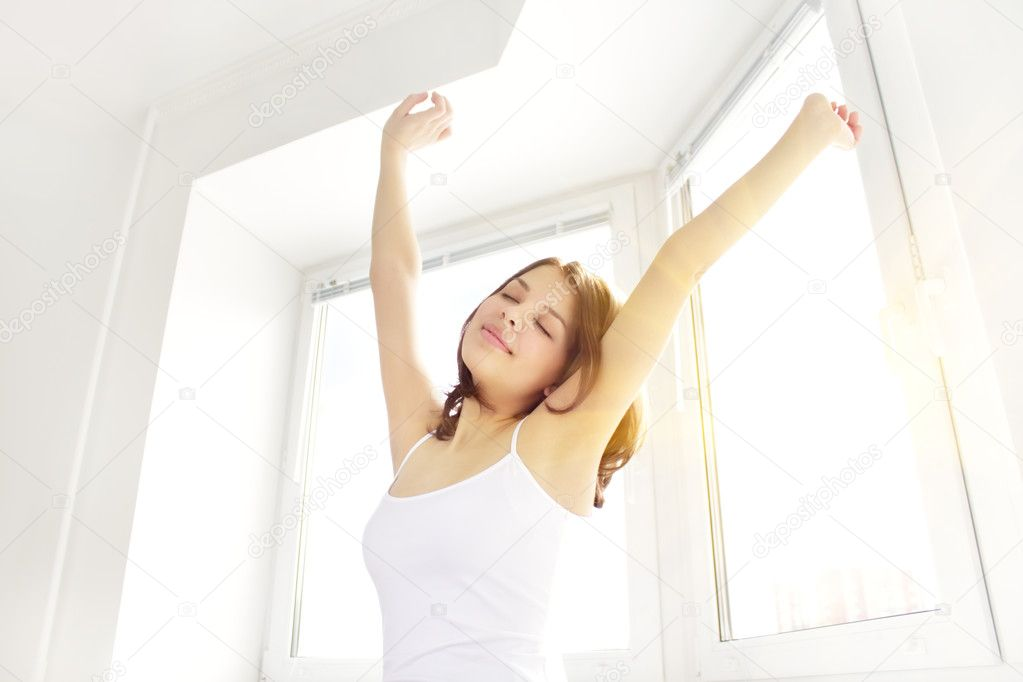 Girl stretching in the morning against the window — Stock Photo #5353128