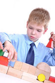 Schoolboy playing with bricks — Stock Photo