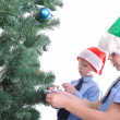 Boys decorating a Christmas tree — Stock Photo