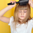 Royalty-Free Stock Photo: Child having problem with brushing her hair