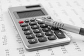 Calculator and pen on a business background — Stock Photo