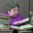 Old woman in library with religious books - Stock Photo