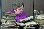 Old woman in library with religious books — Stock Photo