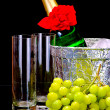Champagne flutes in ice bucket, glasses and grape - Stock Photo