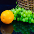 Fresh orange and grape near wooden basket - Stock Photo