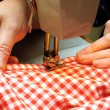 Hands stitching denim cloth with a sewing machine - Stock Photo