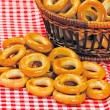 Stock Photo: Basket with bread ring on motley background