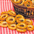 Foto Stock: Basket with bread ring on motley background