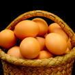 Eggs in a basket on a black background - Stock Photo