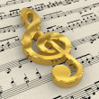 Golden treble clef on score paper — Photo