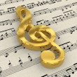 Golden treble clef on score paper — Foto Stock #4033189