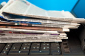 Stack of newspapers on laptop — Stock Photo