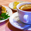 Tea with lemon and cakes — Stockfoto