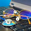 Stethoscope and glasses on black laptop - Stock Photo