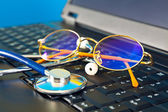 Stethoscope and glasses on black laptop — Stock Photo