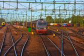 Freight train passing railway station — Stock Photo