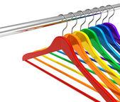 Rainbow hangers on clothes rail — Stock Photo