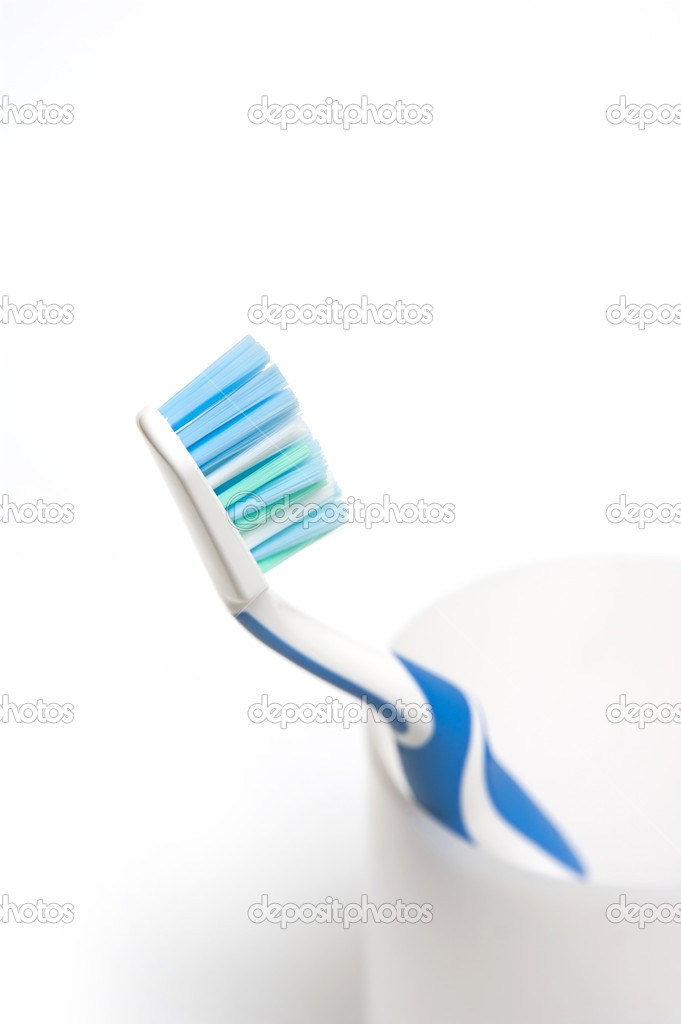 Blue toothbrush in glass. Focus is pointed at the bristle brushes — Stock Photo #5150254