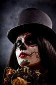 Sugar skull girl in tophat holding dead roses — Stock Photo