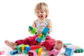 Laughing little boy playing with colorful blocks — Stockfoto