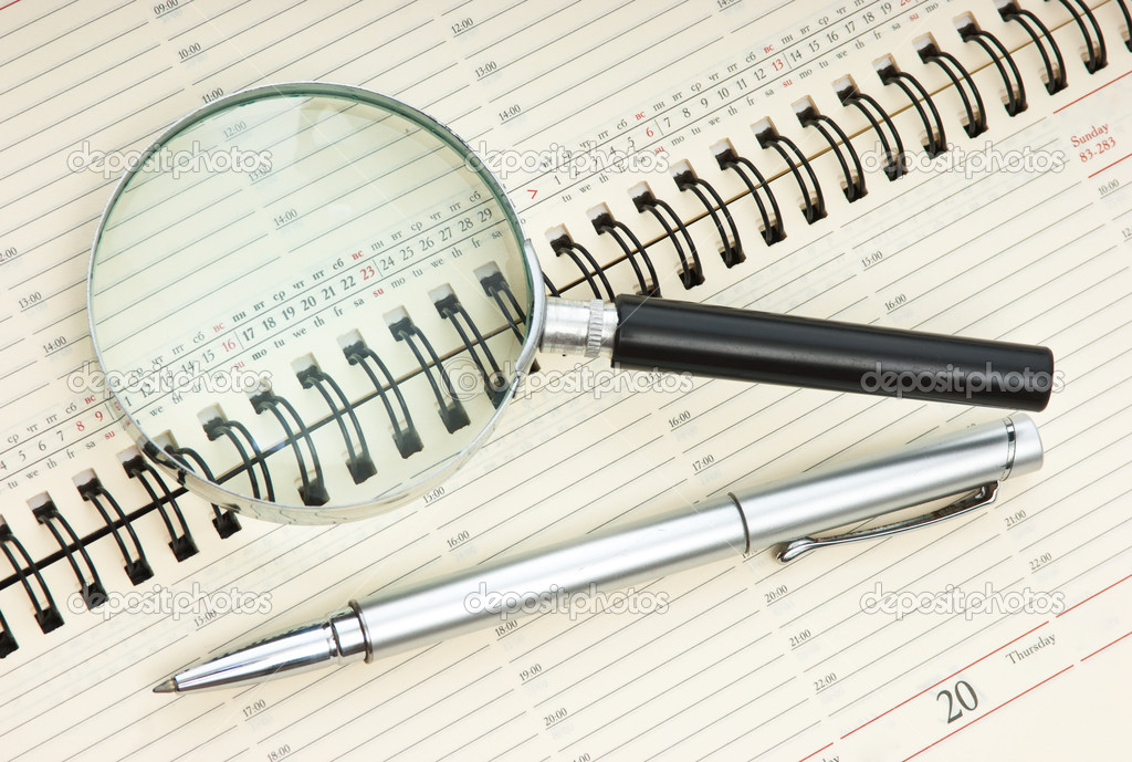 Pen and magnifying glass on the calendar  Stock Photo #3987591