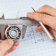 Technical drawing and callipers with bearing in hand - Stock Photo