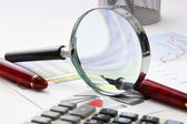 Magnifying glass and the working pape — Stock Photo
