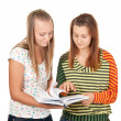 Two teenage girls smiling and reading book — Stock Photo #4928975