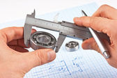 Technical drawing and callipers with bearing in hand — Stock Photo