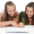 Two teenage girls smiling and reading book — Stock Photo #5326149