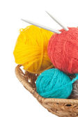 Ball of wool and knitting needles in baske — Stock Photo