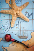 Tobacco pipe and starfish on map — Stock Photo