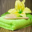 Yellow flower on towel and wooden hairbrush — Zdjęcie stockowe #5063291