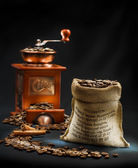 Dark composition of coffee mill and bag — Stock Photo