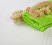 Brush and massager with green towel — Stock Photo