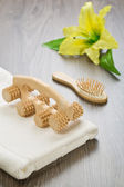 Hairbrush massager and towel with flower — Stock Photo