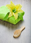 Yellow flower on towel with hairbrush — Stok fotoğraf