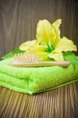 Yellow flower on towel and wooden hairbrush — Stok fotoğraf