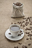 Coffee grains and cup of coffee on sacking — Stock Photo